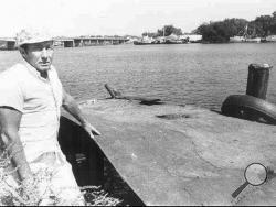 In this 1973 file photograph, Charles Hickson of Pascagoula, Miss., stands on the west bank of the Pascagoula River, close to the site where he claims he and Calvin Parker Jr. were abducted by aliens. (AP Photo/Mississippi Press, File)