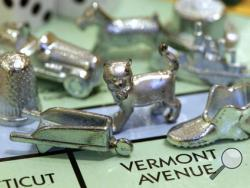 FILE - In this Feb. 5, 2013 file photo, the thimble game piece, left, sits among other Monopoly tokens at Hasbro Inc., headquarters in Pawtucket, R.I. The thimble will no longer be a game piece in Monopoly, rejected in 2017 in a campaign to determine the tokens for the next generation of the game. (AP Photo/Steven Senne, File)