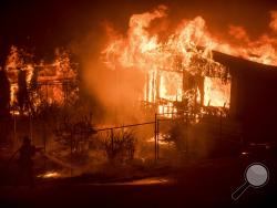 A firefighter sprays water as flames from a wildfire consume a residence near Oroville, Calif., on Sunday, July 9, 2017. Evening winds drove the fire through several neighborhoods leveling homes in its path. (AP Photo/Noah Berger)