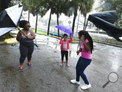 Umbrellas held by Janesse Brown, left, and her daughter Briana Johnson, 12, right, get torn apart by strong winds as Kyra Johnson, 8 watch, while they tried to visit Southbank Riverwalk in Jacksonville, Fla., Sunday, Sept. 10, 2017, as Hurricane Irma passes the area. (Bob Self/The Florida Times-Union via AP)