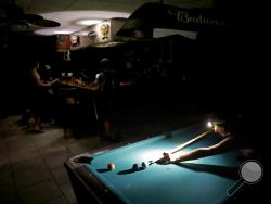 Lisa Borruso plays pool using a headlamp as the power remains out following Hurricane Irma at Gators' Crossroads in Naples, Fla., Monday, Sept. 11, 2017. Statewide, an estimated 13 million people, or two-thirds of Florida's population, remained without power. That's more than the population of New York and Los Angeles combined. Officials warned it could take weeks for electricity to be restored to everyone. (AP Photo/David Goldman)
