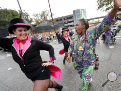 A woman from the crowd jumps in and dances with a dance group as they march in the Krewe of Thoth Mardi Gras parade in New Orleans, Sunday, Feb. 11, 2018. The krewe's original parade route was designed specifically to serve people who were unable to attend other parades in the city. The route passes in front of several extended healthcare facilities. Carnival season will culminate on Mardi Gras day this Tuesday, Feb. 13. (AP Photo/Gerald Herbert)
