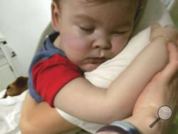 In this April 23, 2018 handout photo provided by Alfies Army Official, brain-damaged toddler Alfie Evans cuddles his mother Kate James at Alder Hey Hospital, Liverpool, England. Kate James and Tom Evans, the parents, said on Facebook that 23-month-old Alfie Evans, who had an incurable degenerative brain condition and was at the center of a legal battle over his treatment, died early morning Saturday April 28, 2018. (Alfies Army Official via AP)