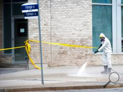 A worker pressure sprays water where one of the victims was killed along Yonge Street the day after a driver drove a van down sidewalks, striking pedestrians in his path in Toronto, Tuesday, April 24, 2018 (Nathan Denette/The Canadian Press via AP)