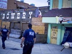 Police patrol past boarded up shops along the boardwalk in Myrtle Beach, S.C., Thursday, Sept. 13, 2018, as Hurricane Florence approaches the east coast. (AP Photo/David Goldman, File)