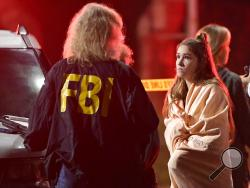 "An FBI agent talks to a potential witness as they stand near the scene Thursday, Nov. 8, 2018, in Thousand Oaks, Calif. where a gunman opened fire Wednesday inside a country dance bar crowded with hundreds of people on ""college night,"" wounding 11 people including a deputy who rushed to the scene. Ventura County sheriff's spokesman says gunman is dead inside the bar. (AP Photo/Mark J. Terrill)"