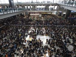 "Protesters surround banners that read: ""Those on the street today are all warriors!"" center top, and ""Release all the detainees!"" during a sit-in rally at the arrival hall of the Hong Kong International airport in Hong Kong, Monday, Aug. 12, 2019. Hong Kong airport suspends check-in for all remaining flights Monday due to ongoing pro-democracy protest in terminal. (AP Photo/Vincent Thian)"