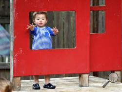 FILE - In this Aug. 27, 2018, Vincent Seeborn, 2, reaches out from a structure on the playground at the Wallingford Child Care Center in Seattle. Child care costs in most states exceed federal subsidy payments provided to low-income parents, according to a newly released report from the Department of Health and Human Services Office of Inspector General, leaving working families with few affordable options. (AP Photo/Elaine Thompson, File)