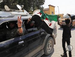 Members of Turkey-backed Syrian National Army (former FSA) flash the V-sign as they drive back to Turkey after they went in for some time on inspection according to the Turkish police entourage in the same area at the border between Turkey and Syria, in Akcakale, Sanliurfa province, southeastern Turkey, Wednesday, Oct. 9, 2019. Turkish President Recep Tayyip Erdogan has long threatened to send troops into northeastern Syria to clear the border region of Syrian Kurdish fighters whom Turkey considers a seriou