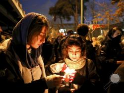 "People gather for a candlelight vigil to remember the victims of the Ukraine plane crash, at the gate of Amri Kabir University that some of the victims of the crash were former students of, in Tehran, Iran, Saturday, Jan. 11, 2020. Iran on Saturday, Jan. 11, acknowledged that its armed forces ""unintentionally"" shot down the Ukrainian jetliner that crashed earlier this week, killing all 176 aboard, after the government had repeatedly denied Western accusations that it was responsible. (AP Photo/Ebrahim Noroo"
