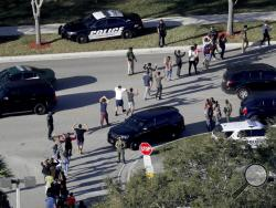 FILE - In this Wednesday, Feb. 14, 2018, file photo, students hold their hands in the air as they are evacuated by police from Marjory Stoneman Douglas High School in Parkland, Fla., after a shooter opened fire on the campus. A Florida law that allows judges to bar anyone deemed dangerous from possessing firearms has been used 3,500 times since its enactment after the 2018 high school massacre. An Associated Press analysis shows the law is being used unevenly around the state. (Mike Stocker/South Florida Su