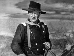"""FILE - In this undated photo, John Wayne appears during the filming of """"The Horse Soldiers."""" In the latest move to change place names in light of U.S. racial history, leaders of Orange County's Democratic Party are pushing to drop film legend Wayne's name, statue and other likenesses from the county's airport because of his racist and bigoted comments. (AP Photo, File)"""