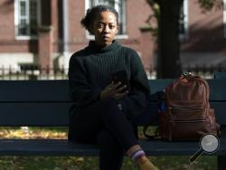Harvard University graduate student Maya James poses in a park near the university, Wednesday, Oct. 14, 2020, in Cambridge, Mass. Law enforcement and voting advocates are warning that con artists are exploiting the election with scams targeting voters. James received an email from a political action committee that seemed harmless: if you support Joe Biden, it urged, click here to check you're registered to vote. Instead, she Googled the name of the group and it didn't exist - a clue the email was a phishing
