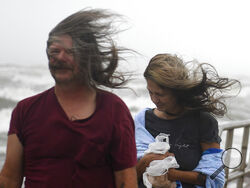 People's hair blows in the wind ahead of Tropical Storm Nicholas, Monday, Sept. 13, 2021, on the North Packery Channel Jetty in Corpus Christi, Texas. Winds are expected to be as high as 60 mph, according to the National Weather Service. (Annie Rice/Corpus Christi Caller-Times via AP)