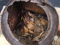 "This image provided by the Saddle Ridge Hoard discoverers via Kagin's, Inc., shows one of the six decaying metal canisters filled with 1800s-era U.S. gold coins unearthed in California by two people who want to remain anonymous. The value of the ""Saddle Ridge Hoard"" treasure trove is estimated at $10 million or more. (AP Photo/Saddle Ridge Hoard discoverers via Kagin's, Inc.)"