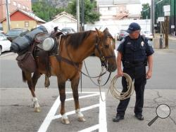 Boulder police look after a horse after its rider was arrested on four charges, including suspicion of riding under the influence and animal cruelty, Monday, Sept. 9, 2013, in Boulder, Colo. (AP Photo/Daily Camera, Mitchell Byars)