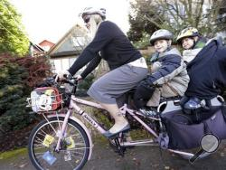 In this photo taken Nov. 27, 2013, Madi Carlson pedals as her sons Rijder, 4, right, and Brandt, 6, ride aboard the family cargo bike as they head to an after-school gym program in Seattle. People in the Pacific Northwest are pushing the limits of what they can carry using so-called cargo bikes, shuttling children, groceries, fish and kegs of beer. (AP Photo/Elaine Thompson)