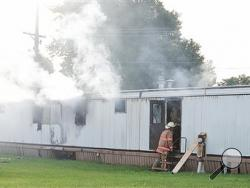 Firefighters extinguish a mobile home fire Sunday, Sept. 15, 2013, that killed a man and five children in Tiffin, Ohio, according to police. Fire crews pulled the man and the children from the home, and all six were taken to Tiffin Mercy Hospital, where they were pronounced dead. The fire was reported shortly before 8 a.m. Sunday in a mobile home park in Tiffin, about 50 miles southeast of Toledo, Ohio. (AP Photo/Advertiser-Tribune, Jill Goshe)