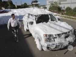 Marco Guerra checks out his car after driving it through chemical foam used as a fire retardant that spilled out from a hangar at San Jose International Airport in San Jose, Calif., Friday, Nov. 18, 2016. A bobbing sea of white foam several feet deep in spots spewed out of a large hangar at the airport, covering cars and blocking businesses as it cascaded onto a nearby street. (Patrick Tehan/Bay Area News Group via AP)