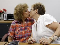Ellen Toplin, right, and Charlene Kurland kiss as they obtain a marriage license at a Montgomery County office despite a state law banning such unions, Wednesday, July 24, 2013, in Norristown, Pa. The chairman of the Montgomery County commissioners, Democrat Josh Shapiro, said he supports same-sex marriage and was ready for the county to defend the stance in court. (AP Photo/Matt Rourke)