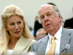 FILE - In this July 25, 2006, file photo, Oklahoma energy tycoon T. Boone Pickens, right, with his wife, Madeleine, appear at a House Energy and Commerce subcommittee hearing on Capitol Hill in Washington. A federal lawsuit accuses Madeleine Pickens, the ex-wife Pickens, of racial discrimination at her rural Nevada dude ranch. (AP Photo/Dennis Cook, File)