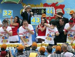 From left to right, Tim Janus, Joey Chestnut, Matt Stonie, and Erik Denmark compete during the Nathan's Famous Fourth of July International Hot Dog Eating contest at Coney Island, Friday, July 4, 2014, in New York. Chestnut won his eighth contest by finishing 61 hotdogs and buns. (AP Photo/John Minchillo)