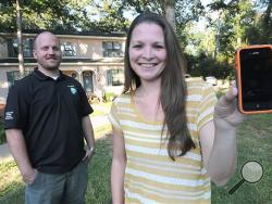 Angela Dalton shows her iPhone that she accidentally dropped out of an airplane over Dothan, Ala. and landed in the front yard of Eric Hall, left, Tuesday, Oct. 1, 2013. (AP Photo/The Dothan Eagle, Danny Tindell)