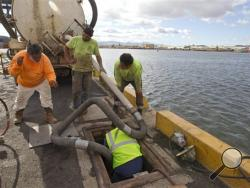 Workers from Pacific Environmental Corporation pumped out a broken Matson pipeline located under the neighboring Horizon shipyard dock in Honolulu Hawaii on Wednesday Sept. 11, 2013. An estimated 233,000 gallons of molasses spilled into the water on Monday. (AP Photo/Honolulu Star-Advertiser, Cindy Ellen Russell)