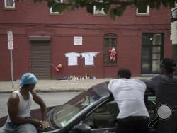 Onlookers stand across the street from a memorial to Lawrence Campbell, who allegedly shot and killed 23-year-old Jersey City police officer Melvin Santiago, Monday, July 14, 2014, in Jersey City, N.J. Campbell was also killed at the scene after police officers returned fire. (AP Photo/John Minchillo)