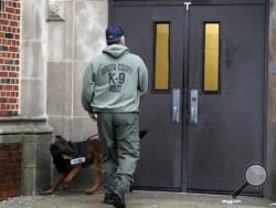 A Bergen County Police officer walks with a police dog outside of Teaneck High School, where at least 60 students were arrested during an overnight break-in, Thursday, May 1, 2014, in Teaneck, N.J. Officers responded to a burglar alarm at the school around 2:30 a.m. Thursday, found urine in the hallways, petroleum jelly on doorknobs, desks flipped over and balloons throughout the building. (AP Photo/Julio Cortez)