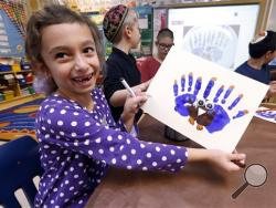 Second-grader Rozie Aronov, 7, holds up a menurkey, a paper-and-paint mashup of a menorah and turkey she created at Hillel Day School in Farmington Hills, Mich., Wednesday, Nov. 20, 2013. The recent class project reflects one way for Jews in the United States to deal with a rare quirk of the calendar that overlaps Thanksgiving with the start of Hanukkah. The last time it happened was 1888 and the next time is 79,043 years from now _ by one estimate that's widely repeated in Jewish circles. (AP Photo)