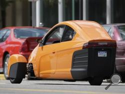 The Elio, a three-wheeled prototype vehicle, is shown in traffic in Royal Oak, Mich., Thursday, Aug. 14, 2014. Instead of spending $20,000 on a new car, Paul Elio is offering commuters a cheaper option to drive to work. His three-wheeled vehicle The Elio will sell for $6,800 car and can save on gas with fuel economy of 84 mpg. (AP Photo/Paul Sancya)