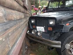 This photo provided by the Myrtle Creek Police Department shows a Jeep that authorities say a toddler crashed into an home in Myrtle Creek, Ore. The 3-year-old boy wearing only a diaper climbed into the Jeep on Tuesday, July 24, 2014, and knocked it out of gear, according to authorities. Witnesses said it rolled down the street, through an intersection and into the house, causing minor damage. After the crash authorities said the toddler ran back to his home to watch cartoons. (AP Photo/Myrtle Creek Police)