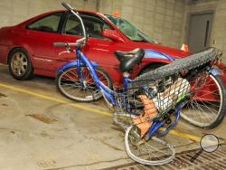 This Jan. 21, 2014 photo shows Steven Gove's three-wheeled tricycle and the car that hit him Saturday night at the Manitowoc, Wis., Police Station. Gove says he was struck Saturday, Jan. 18, 2014 night while riding his three-wheeled bicycle. Gove says he was wearing an overcoat with a reflective vest and he had front and rear flashers on. He says he's not sure why the driver didn't see him. Police have arrested a 20-year-old Manitowoc man in the crash. (AP Photo/Herald-Times Reporter, Sue Pischke)