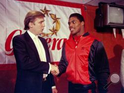 FILE - In this March 8, 1984, file photo, New Jersey Generals owner Donald Trump, left, shakes hands with Herschel Walker at a news conference in New York, after agreeing on a four-year contract. As President-elect Trump came of age as a public figure during the 1980s, he opened up a refurbished Grand Hyatt on 42nd Street, took over the long-stalled renovation of Central Park's ice skating rink and purchased the New York-area team in the fledgling United States Football League. (AP Photo/Dave Pickoff, File)