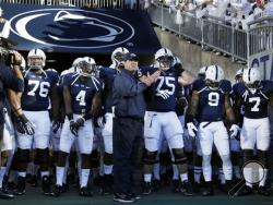 Penn State head coach Bill O' Brien , center, waits in the tunnel leading to the field with his team before an NCAA college football game against Central Florida in State College, Pa., Saturday, Sept. 14, 2013. Central Florida won 34-31. (AP Photo/Gene J. Puskar)