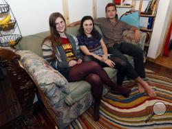 From left, Lara Russo, Cally Guasti and Reese Werkhoven sit on a couch in their apartment in New Paltz, N.Y. on Thursday, May 15, 2014. The roommates had purchased it at a Salvation Army store and found $40,800 stashed inside. After finding a deposit slip, they returned the money to the 91-year-old upstate New York widow who had hidden it there. (AP Photo/Mike Groll)