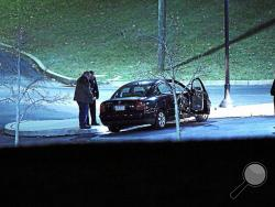 Police investigate a car, left, at the athletic center of Widener University in Chester, Pa. after a student was shot Monday, Jan. 20, 2014. Authorities warned students to remain indoors until further notice. (AP Photo/Delaware County Daily Times, Robert J. Gurecki)