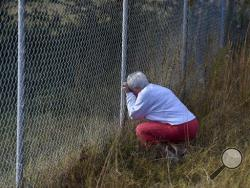 Frances Bradley prays at the fence adjoining their properties in Woodruff, S.C. Sunday, Nov. 6, 2016. Kohlhepp, accused of holding a woman chained inside a storage container, was due in court for a bond hearing Sunday after investigators say he confessed to an unsolved quadruple murder that happened 13 years ago. He's also charged with the woman's kidnapping, and prosecutors say more charges are expected. (AP Photo/Richard Shiro)