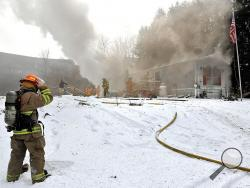Smoke pushes out of the roof of a trailer home as firefighters attack the blaze Friday morning on Mountain Road in Fishing Creek Township. (Press Enterprise/Jimmy May)