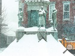 Snow slides off the Civil War monument on Market Square, piling up to the base of each of the veteran's feet Tuesday morning. (Press Enterprise/Keith Haupt)