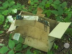 An opened package sits along a trail between Catherine Street and Park Place Village in Bloomsburg. (Press Enterprise/Julye Wemple)