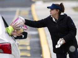 Cafeteria worker Cathy Piluso hands out free meals at Bensalem High School in Bensalem, Pa., Thursday, March 19, 2020.Pennsylvania reported another big jump in confirmed coronavirus Thursday. The state Department of Health reported that cases topped 180, up 40%. (AP Photo/Matt Rourke)