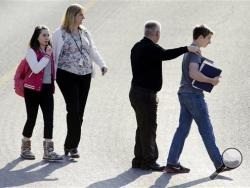 Students and guardians walk to their car from the Franklin Regional Middle School after more then a dozen students were stabbed by a knife wielding suspect at Franklin Regional High School on Wednesday, April 9, 2014, in Murrysville, Pa., near Pittsburgh. The suspect, a male student, was taken into custody and is being questioned. (AP Photo/Tribune Review, Brian F. Henry)