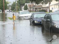 Craig DiDio Jr., 4, walks through floodwater on Spring Garden Avenue on Thursday afternoon. (Press Enterprise/Susan Schwartz)