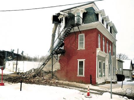 A demolition crew from Columbia Excavating tears down a three-story apartment house at 114 Main St. in Catawissa, on Tuesday, as part of a government flood buyout. For many years the structure was the home of the Catawissa Fraternal Order of Eagles No. 794.