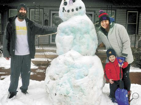Seth McCloughan, Amanda Wolcott and their son, Killian McCloughan, 2, stand with the large snowman they made in front of their West Main Street home in Bloomsburg on Monday.
