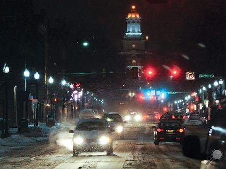 Vehicles move along a snow-covered Main Street in Bloomsburg Monday night.