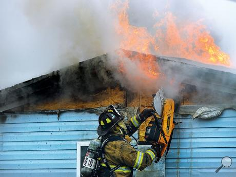 A firefighter uses a saw to open the wall and expose the flames at this home on Tower Drivein Montour Township on Friday morning.