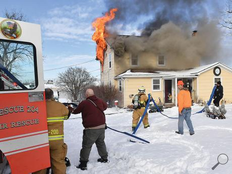 Firefighters from Lime Ridge geta hand from police and local residents, puling ahose line off the first-arriving apparatus at Friday afternoon's fire along Haskell Lane in Mifflin Township.